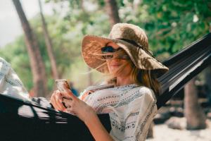 Femme avec chapeau et lunettes de soleil en train de bronzer sur un hamac