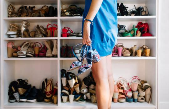 femme portant une robe bleue se tenant devant un placard plein de chaussures